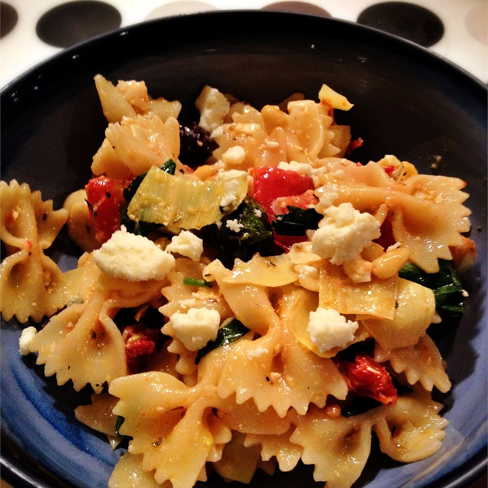 An easy vegetarian pasta dish that's packed with feta cheese, sun-dried tomatoes, olives, and pine nuts. Toast the pine nuts in a dry skillet until golden, and add freshly chopped basil for added flavor. Leftovers are delicious served as a pasta salad.