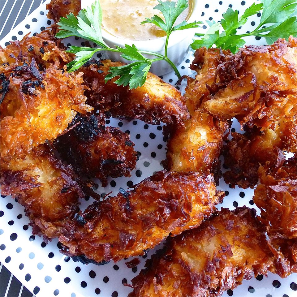 """Shrimp are first dipped in a simple beer batter, then coated with sweetened coconut and fried in batches until crispy. """"Great recipe. My family loved it,"""" said reviewer Tara. """"I let the shrimp sit in the fridge for 30 minutes after they were breaded so that the coating would really stick before putting them in the fryer."""""""