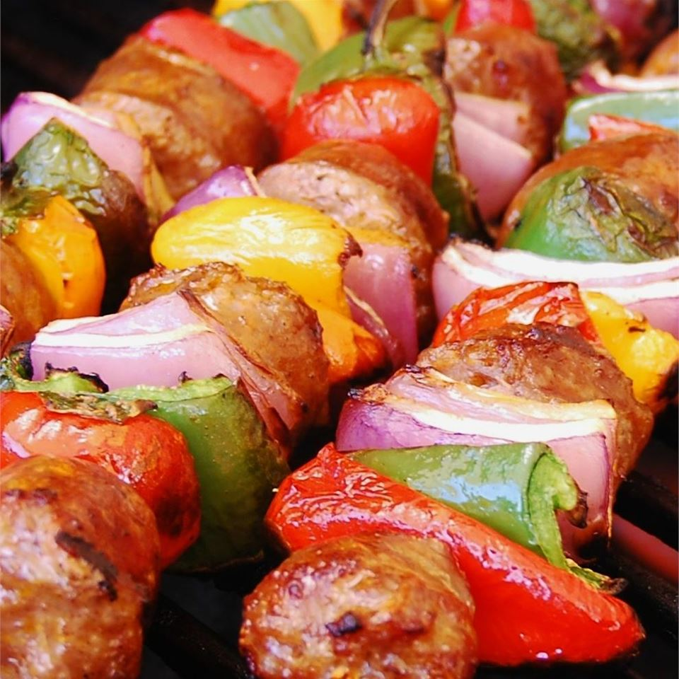 """Sausages marinate in beer with red bell peppers, jalapeno peppers, and red onions. String disks of sausage and pieces of veggies onto skewers and grill, melting provolone cheese over the top during the final few minutes of cooking. Bd.weld rates it 5 stars: """"Spicy good. I use shredded provolone hot Italian sausage and different colored peppers along with the jalapeno. These are really good with or without the provolone."""""""