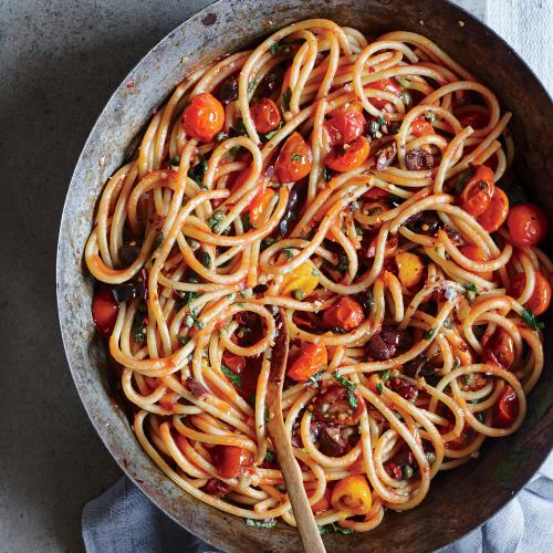 Bucatini Puttanesca: Tomatoes simmer with anchovies, olives, and capers for a tangy, rustic meal sure to please all tastebuds.