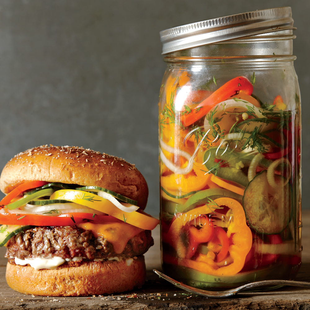 Cheesesteak Burgers with Pickled Peppers, Onions, and Cucumber: We crown the summer classic with a pile of crunchy, pickly vegetables. Quick pickles add tangy crunch to our fresh riff on the cheesesteak sandwich.