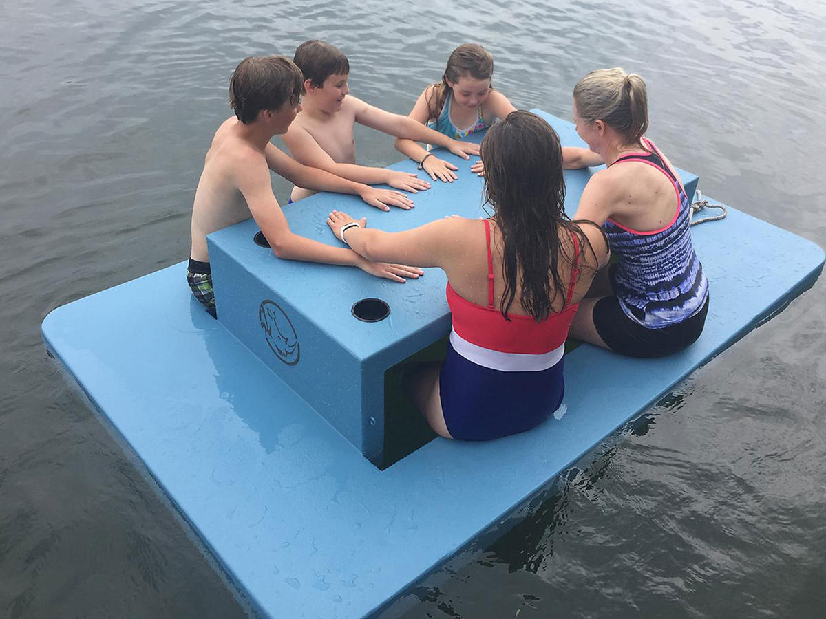 kids using floating picnic table in water