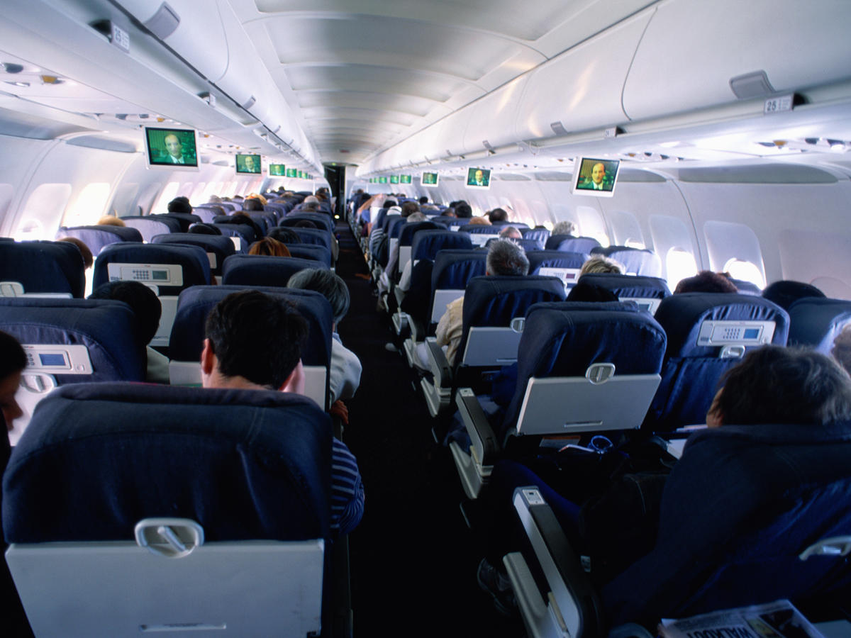 Passengers sitting in commercial airliner, rear view