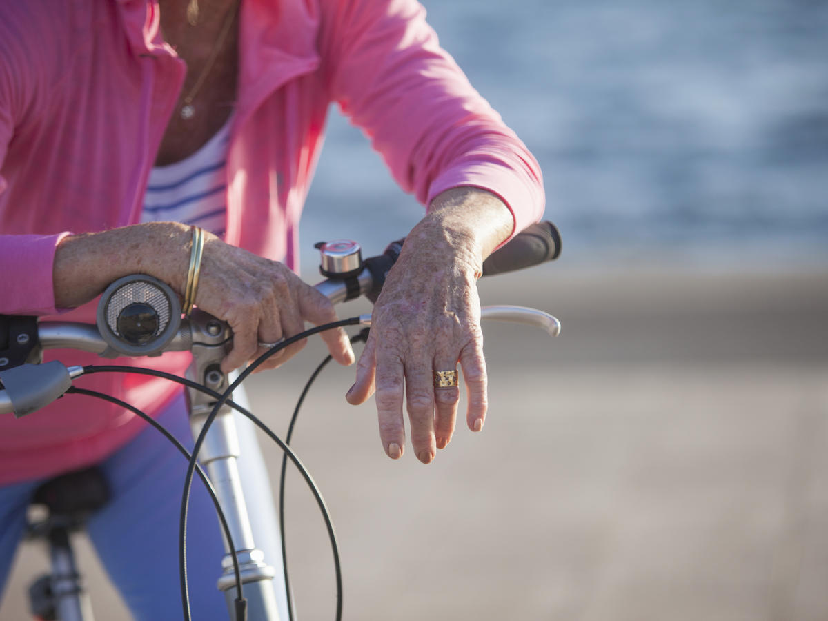 Senior woman on bicycle by beach