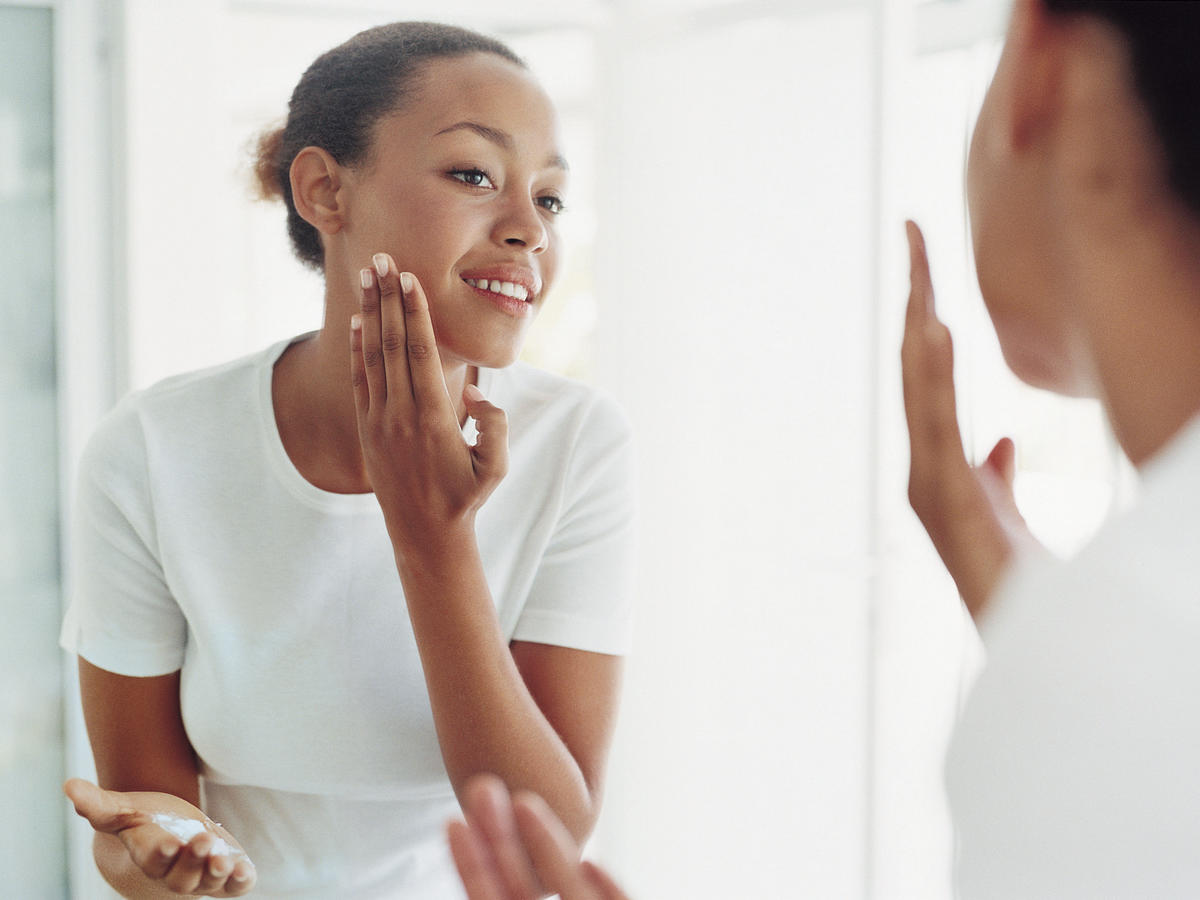 Woman applying hair removal cream on face in mirror