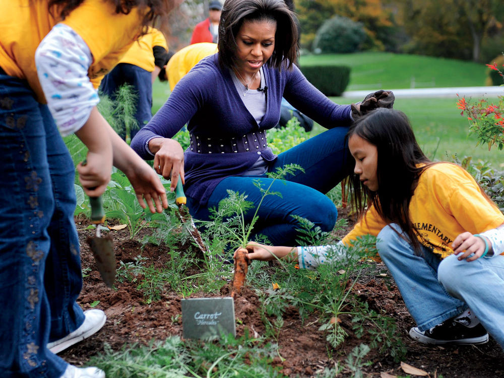 Harvesting carrots in the White House kitchen garden with elementary school students in 2009