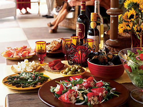 Use unique pieces. The bright red candle in the center of the table, encased in a curlicue iron holder is one of Gautro's favorite details of this Old-Madrid inspired tapas table.