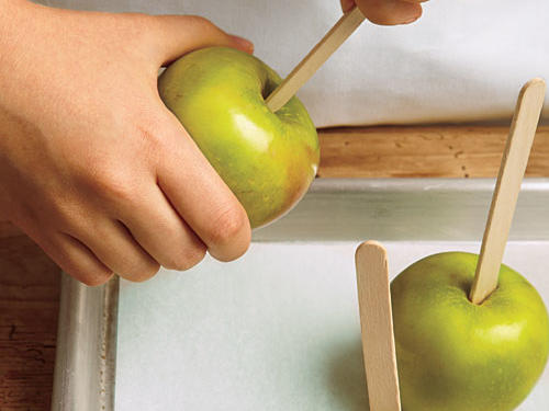 Push wooden sticks into apples