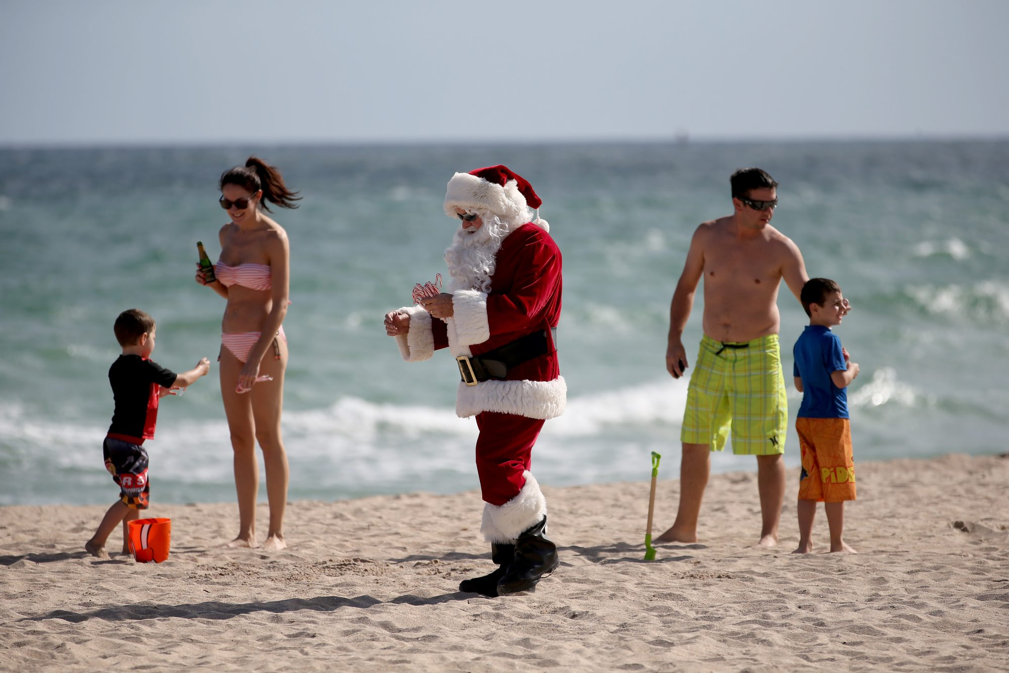 Tom Tapp dressed as Santa Claus walks along the beach passing out candy canes and posing for pictures with beach goers on December 20, 2013 in Fort Lauderdale, Florida.