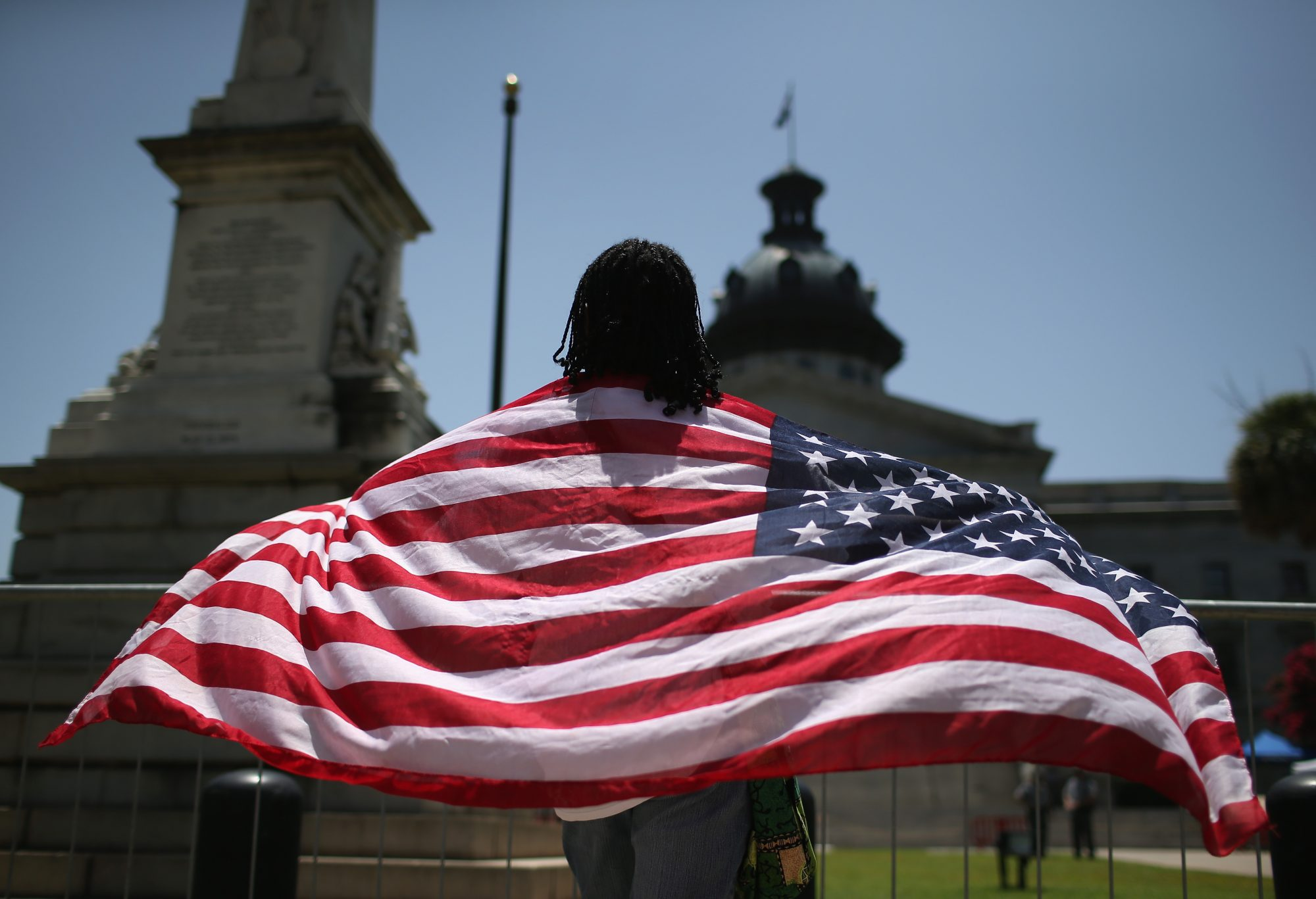 South Carolinan Brenda Brisbon wears the 'Stars and Stripes' after the Confederate 'Stars and Bars' was lowered from the flagpole in front of the statehouse on July 10, 2015 in Columbia, South Carolina.