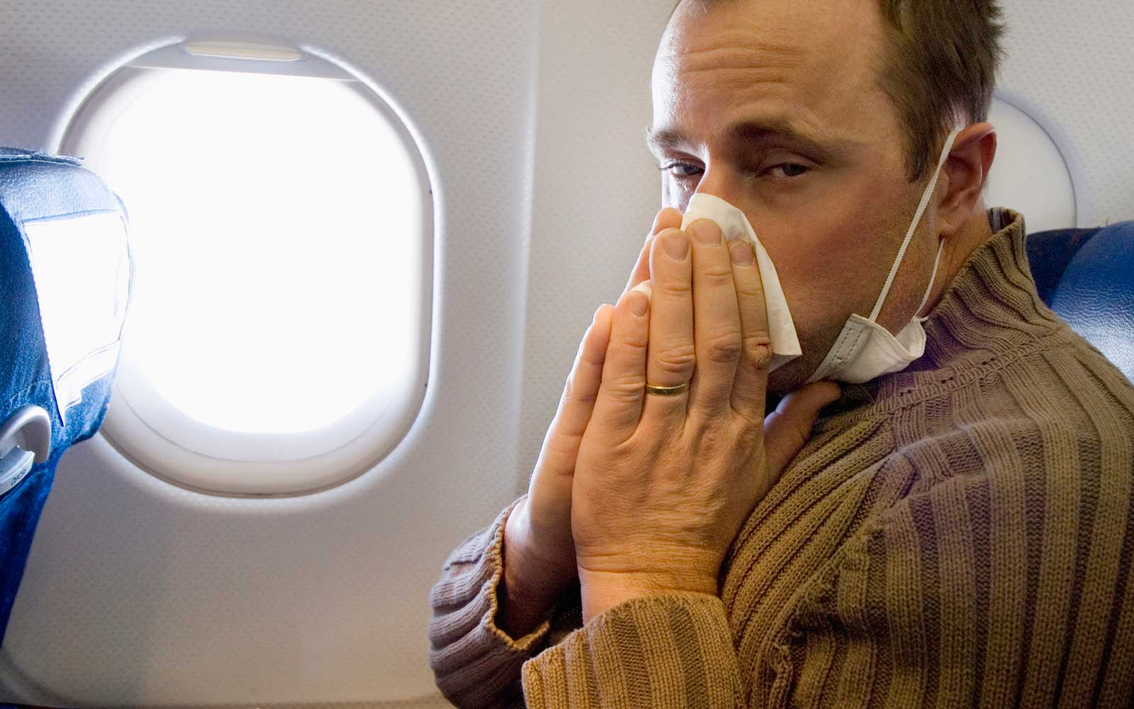 Man with influenza on airplane