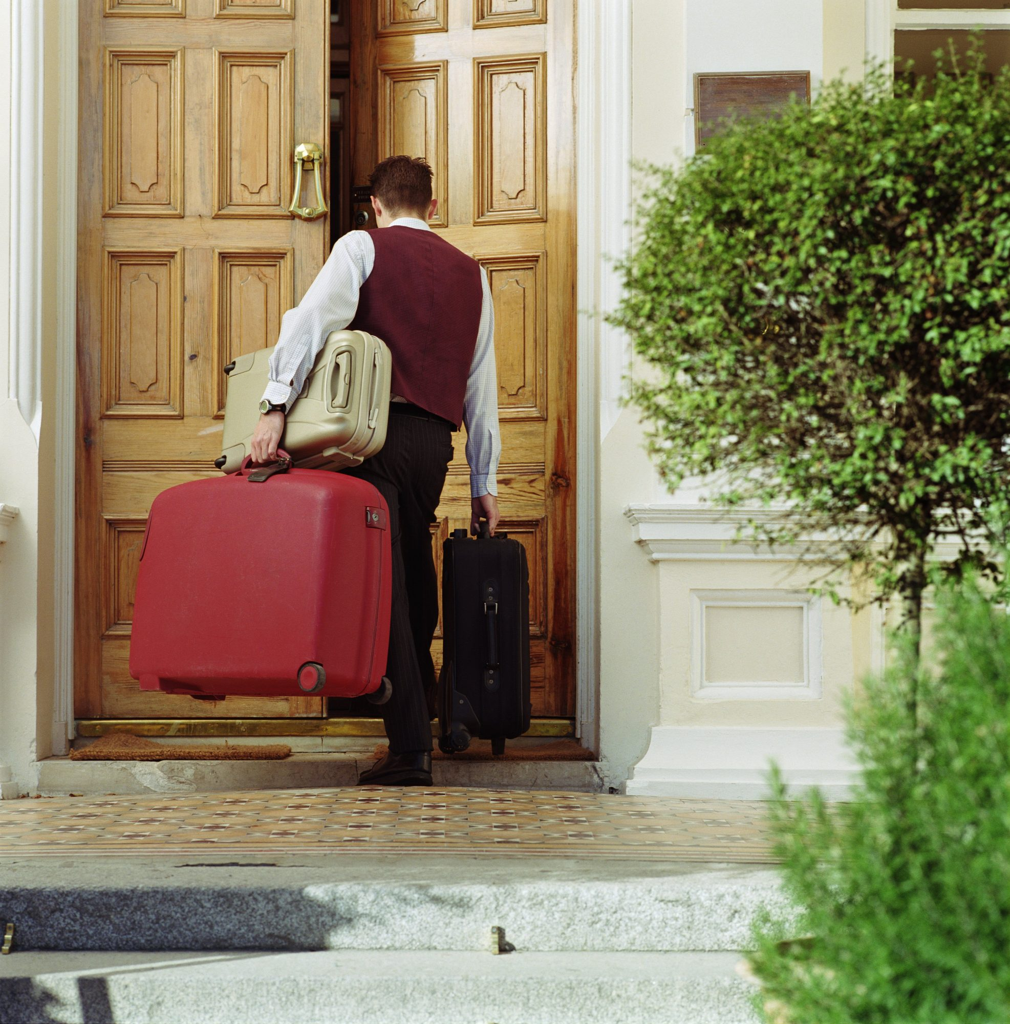 Doorman carrying luggage into hotel, rear view