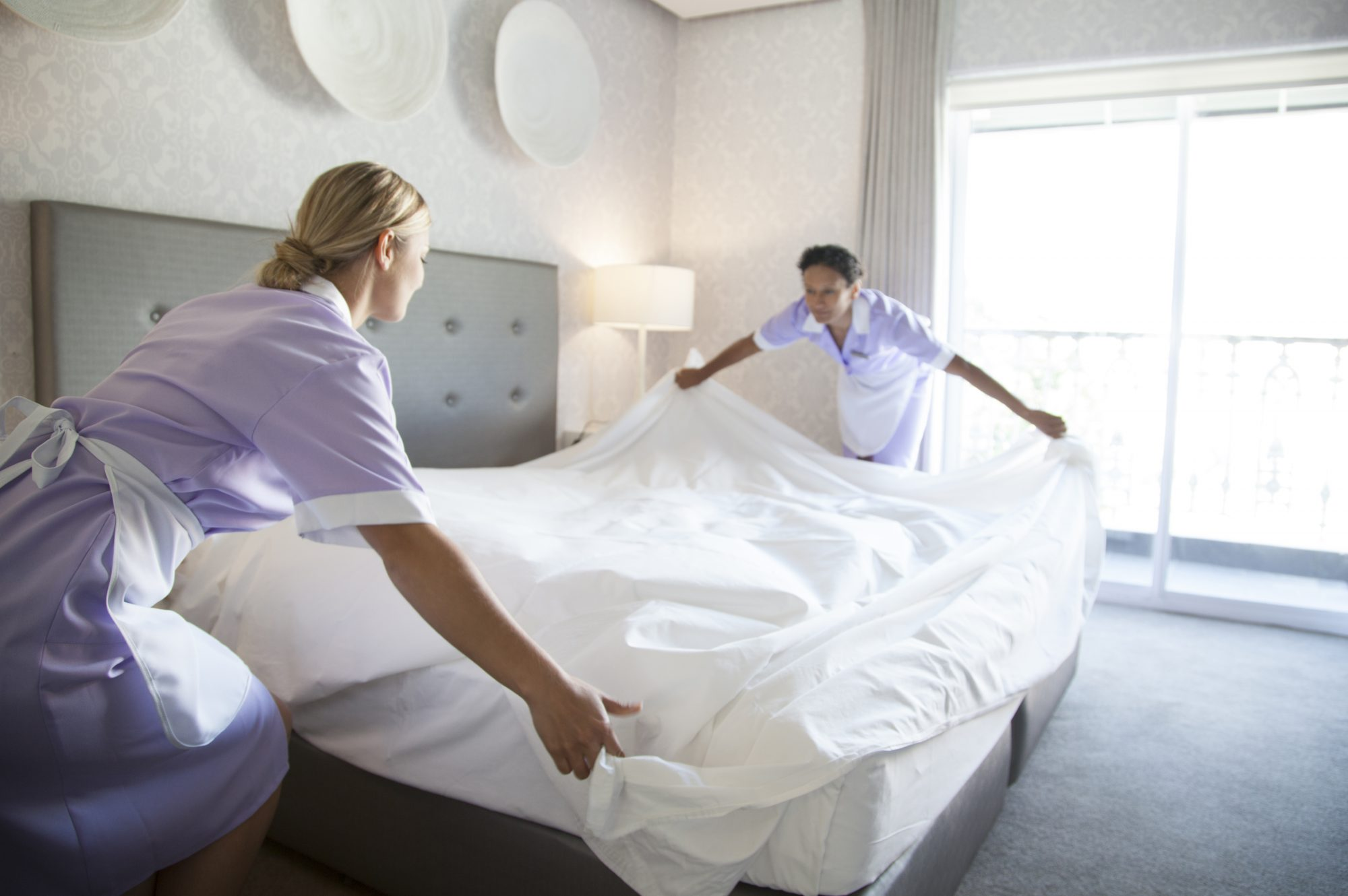 Chambermaids making bed in hotel room