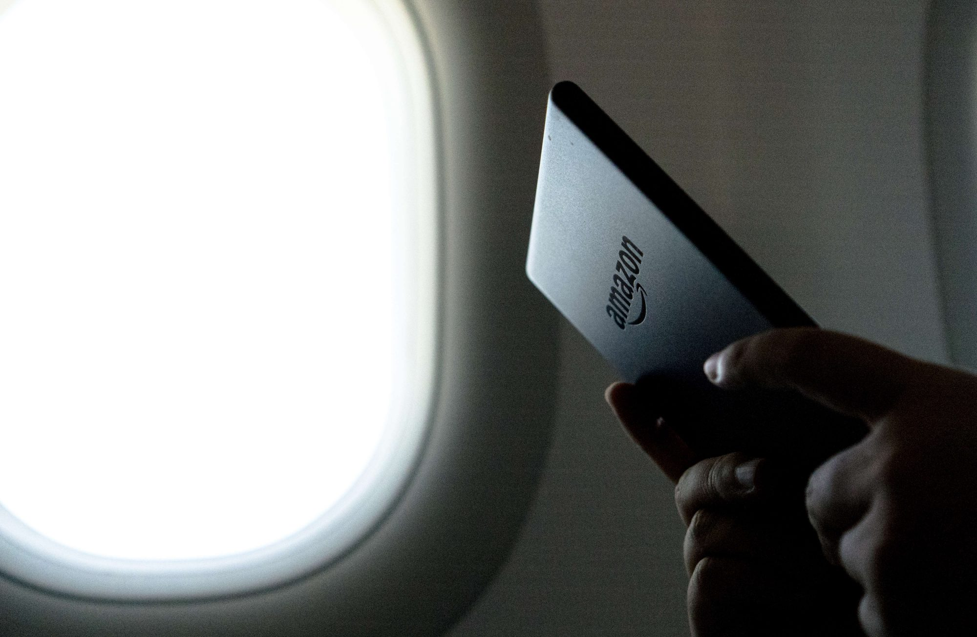 A person reads a kindle ebook on an airplane.  Amazon