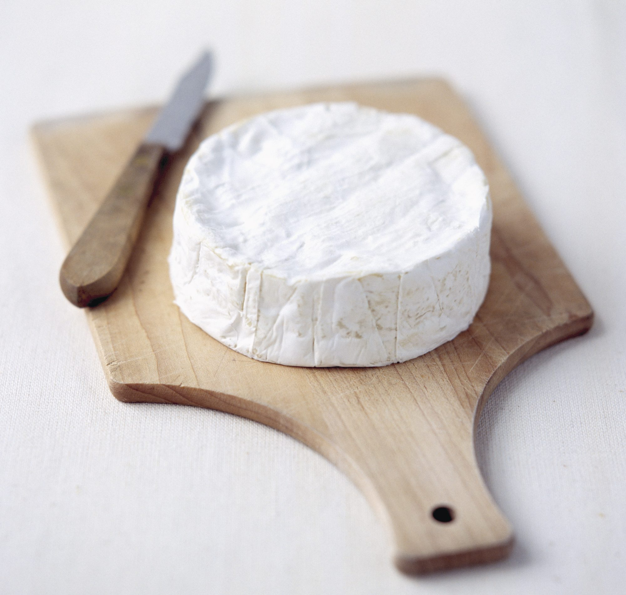 wheel of brie cheese on wooden board