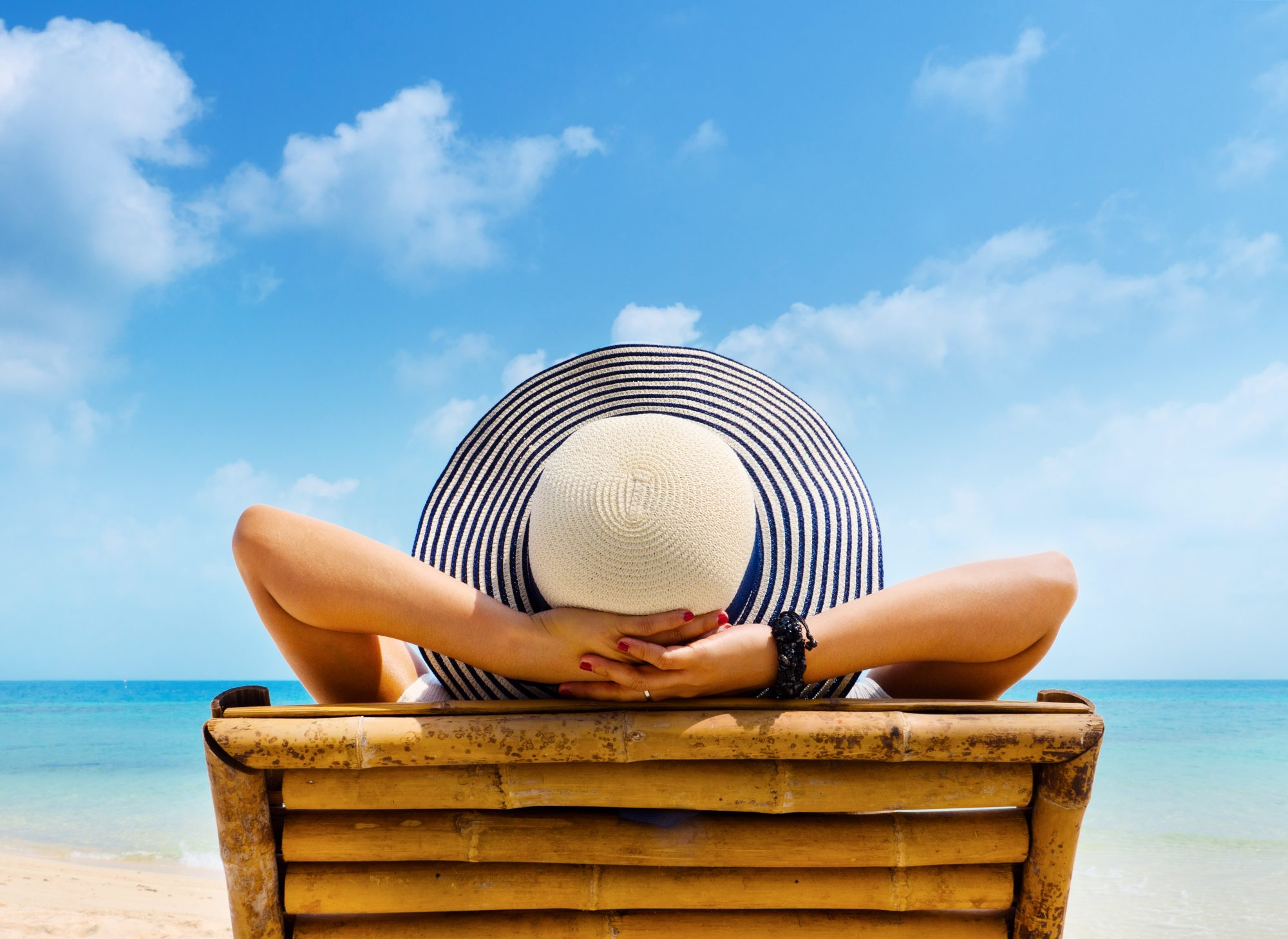 Woman Sitting in Lounge Chair with Sunhat
