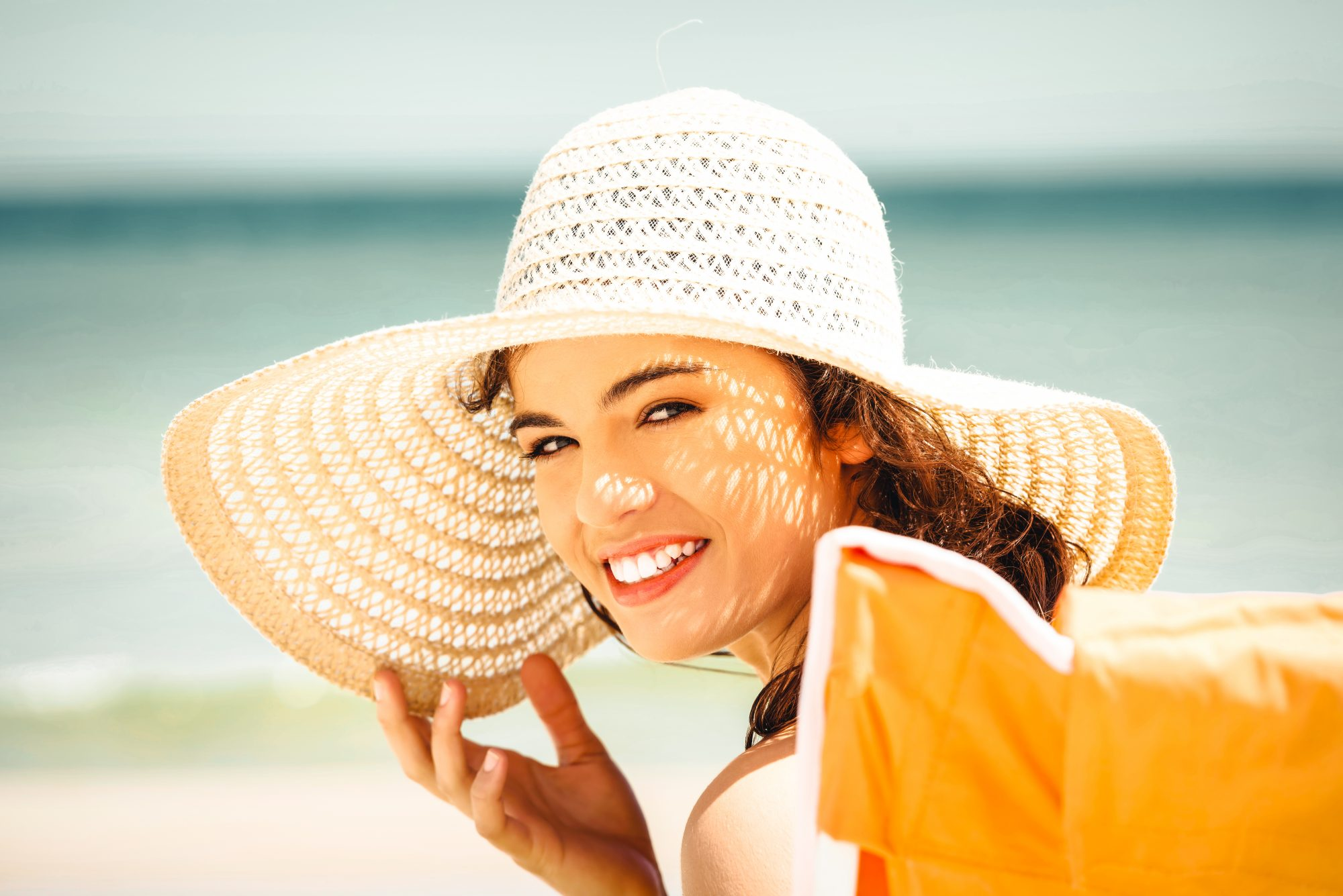 Woman in Sunhat Smiling on the Beach