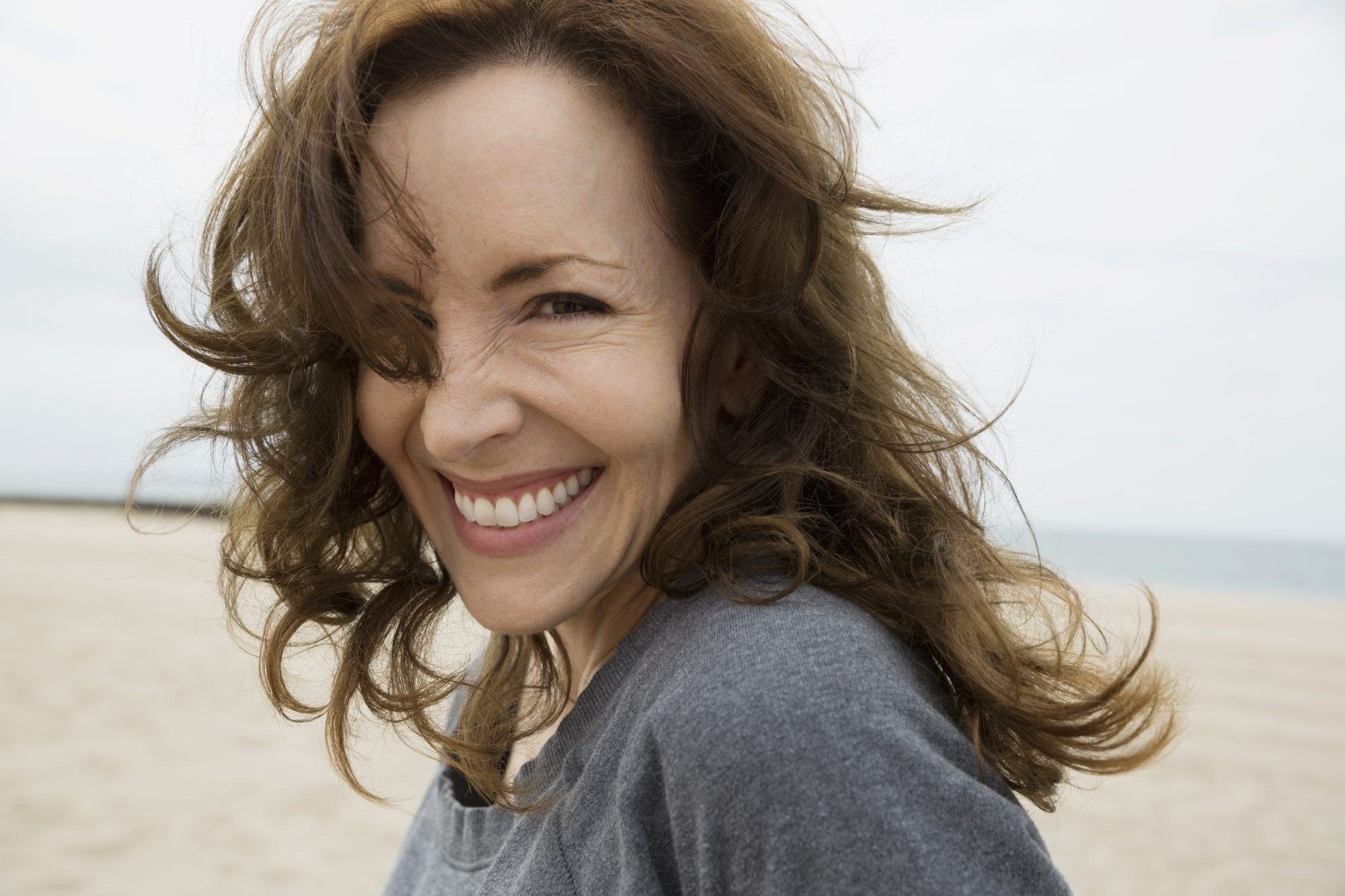 Woman Walking on Beach with Hair Blowing