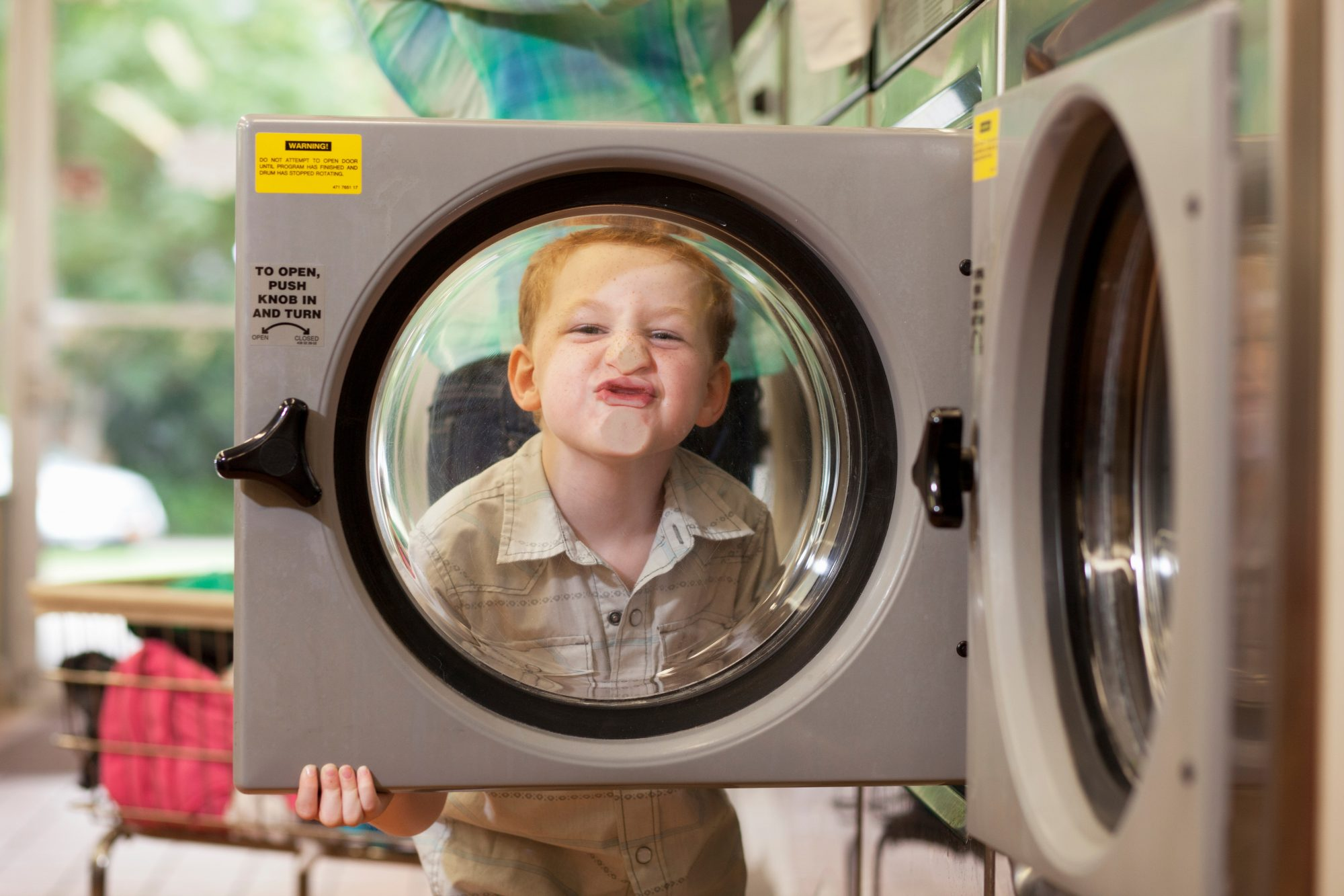 little boy in washing machine door