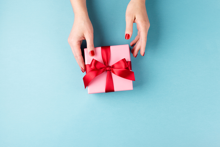 Female hands holding gift box on blue background.