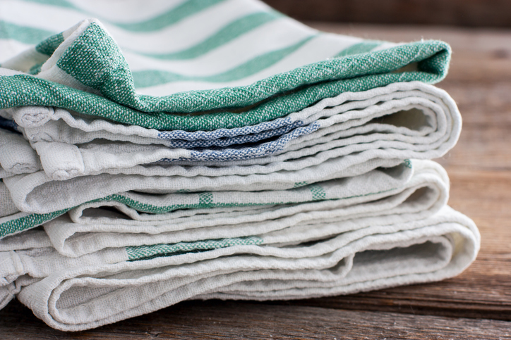Clean kitchen towels stacked in a basket on the basket, selective focus