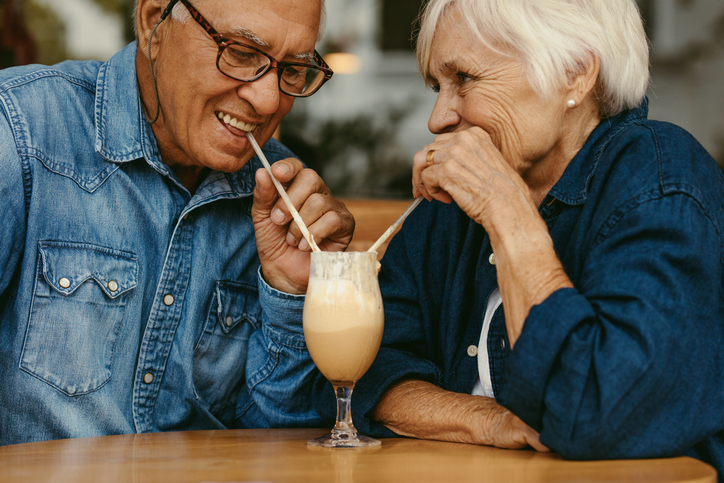 Senior couple in love drinking cold coffee from one glass