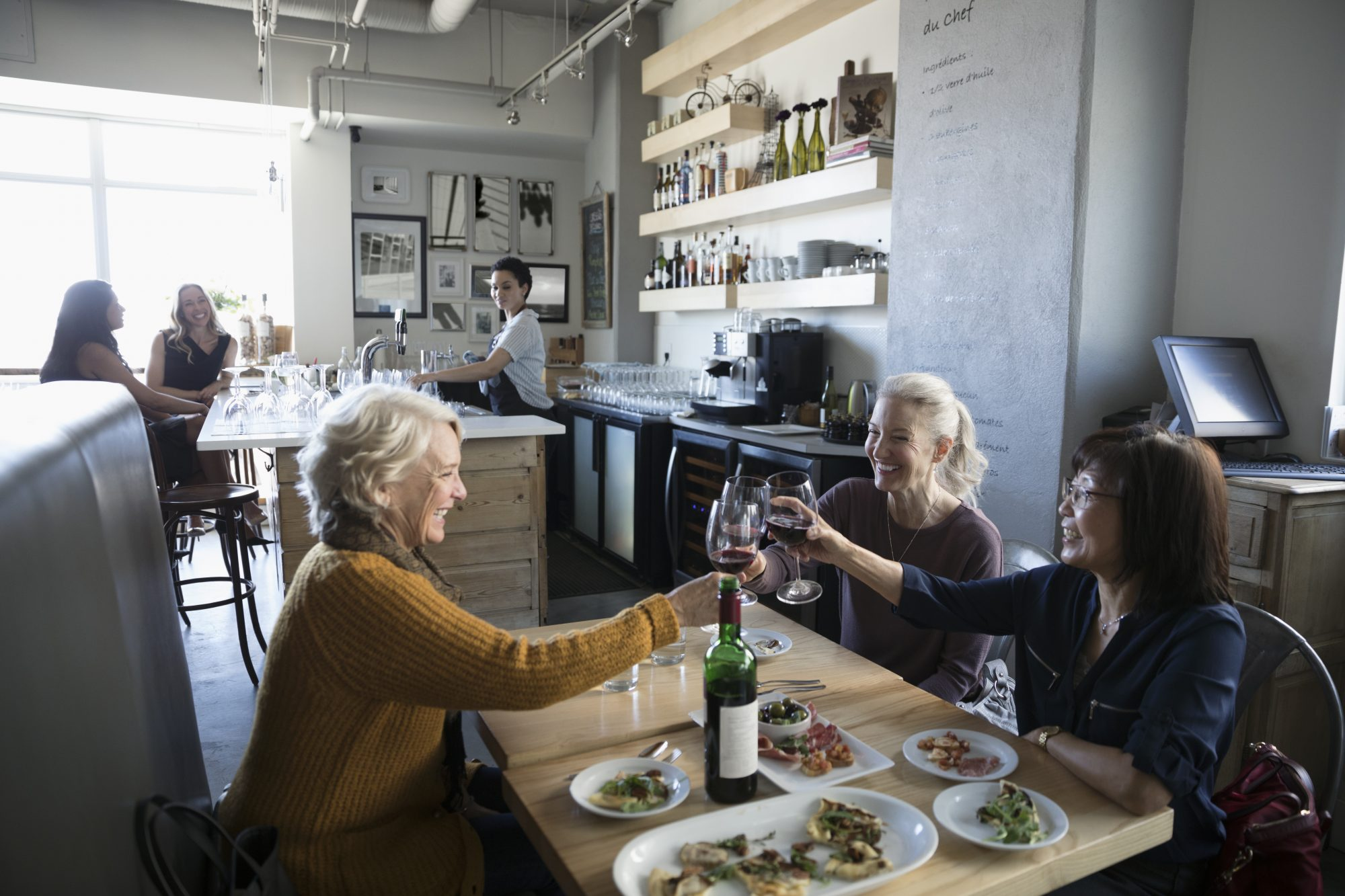 Older Women Eating at Restaurant Cheers with Wine