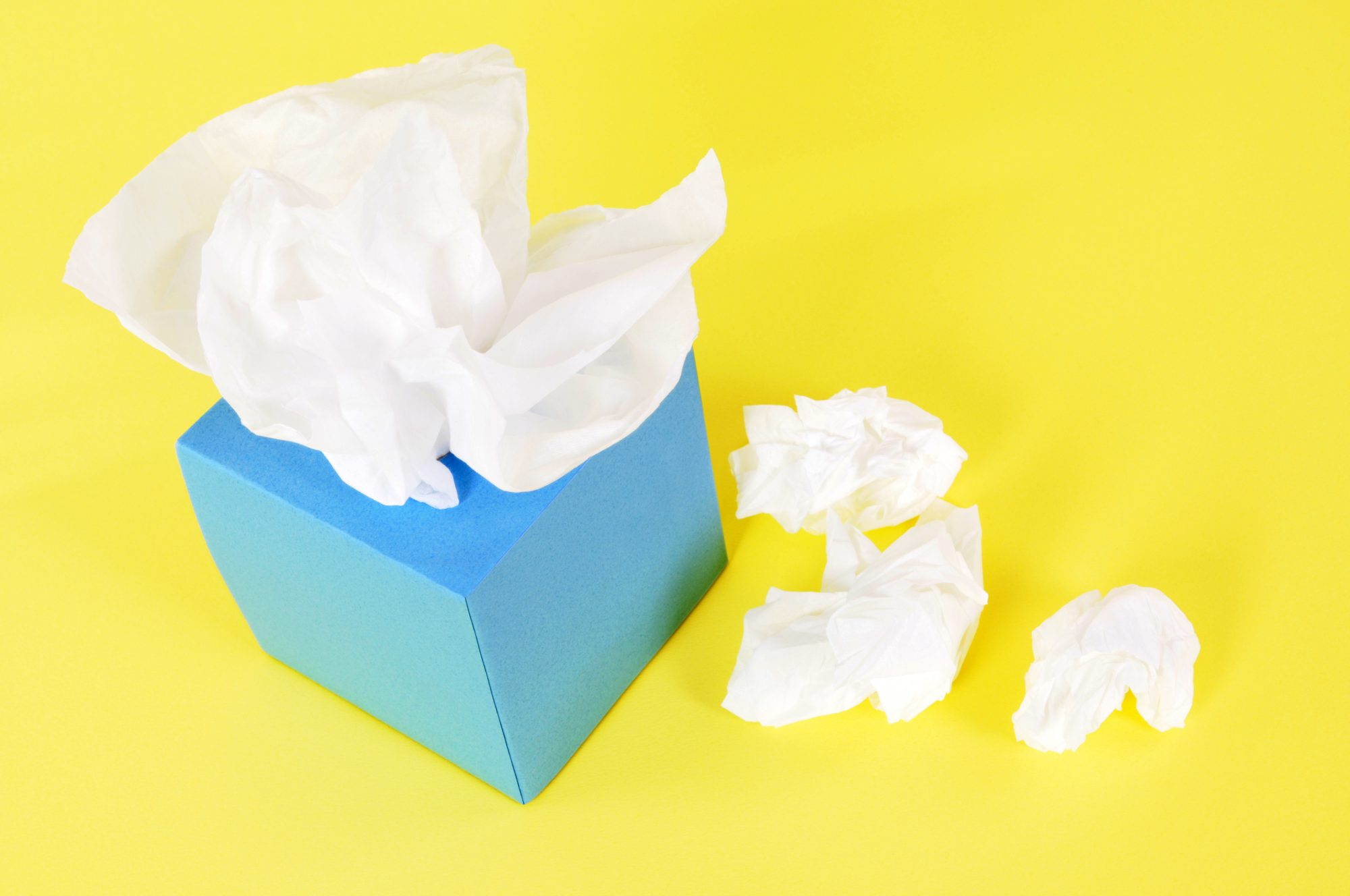 Blue tissue box with crumpled tissues beside it