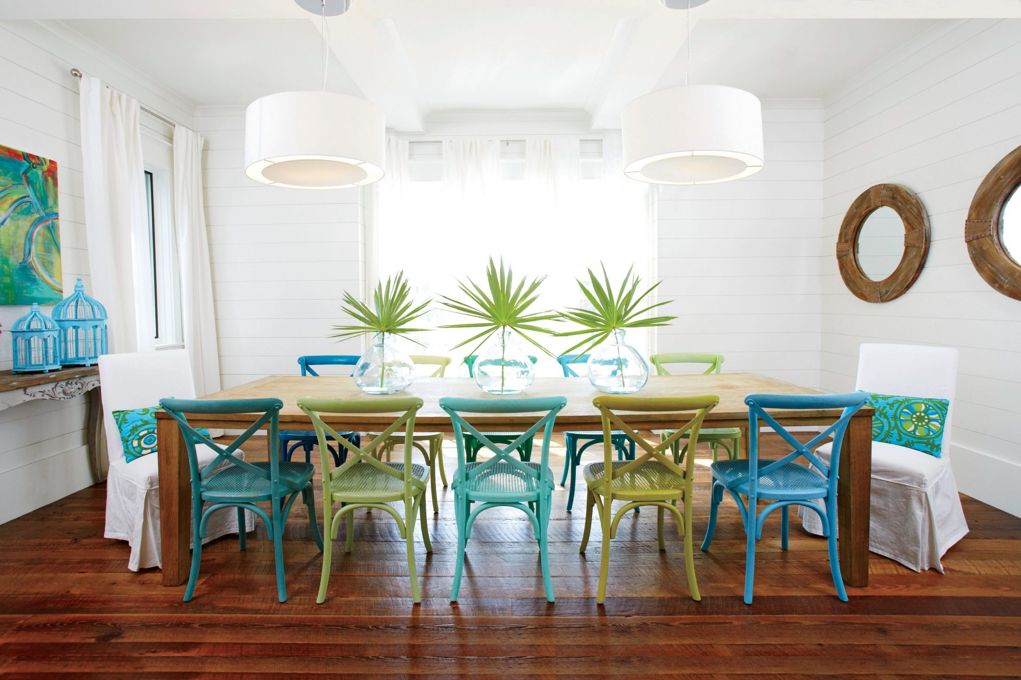 For a cheerful, ultra-casual vibe, the homeowners of this Florida beach house spray-painted wooden side chairs from Restoration Hardware in varying shades of blue and green.