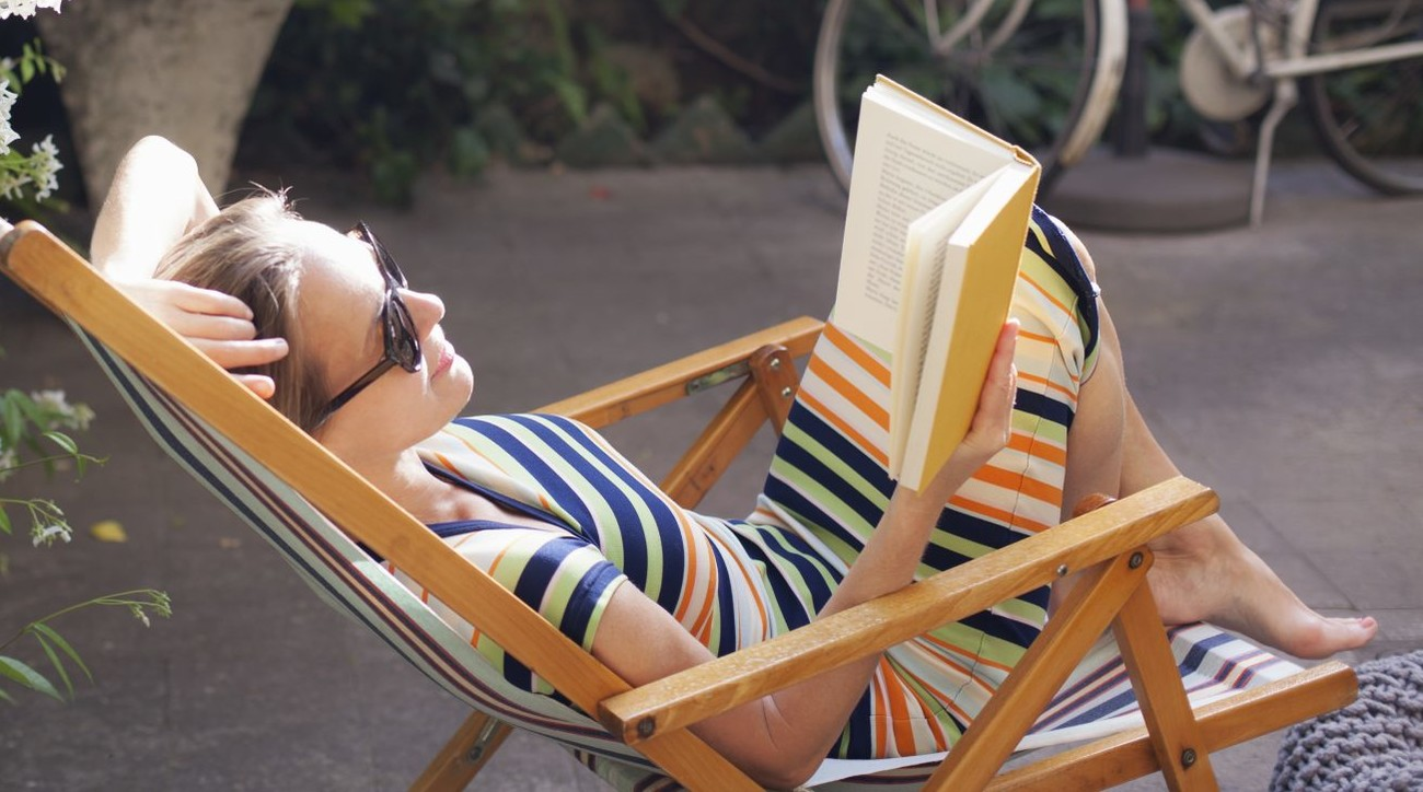 Woman relaxing on deck chair in backyard, reading a book