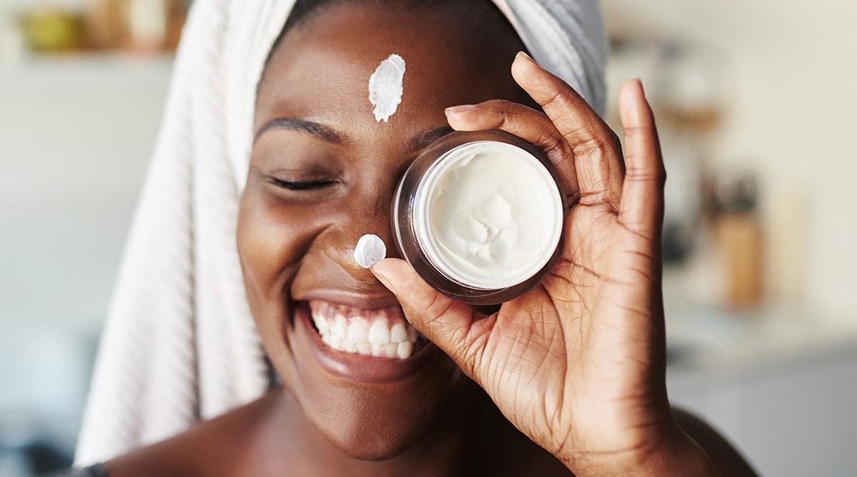 beautiful young woman holding up a face cream product