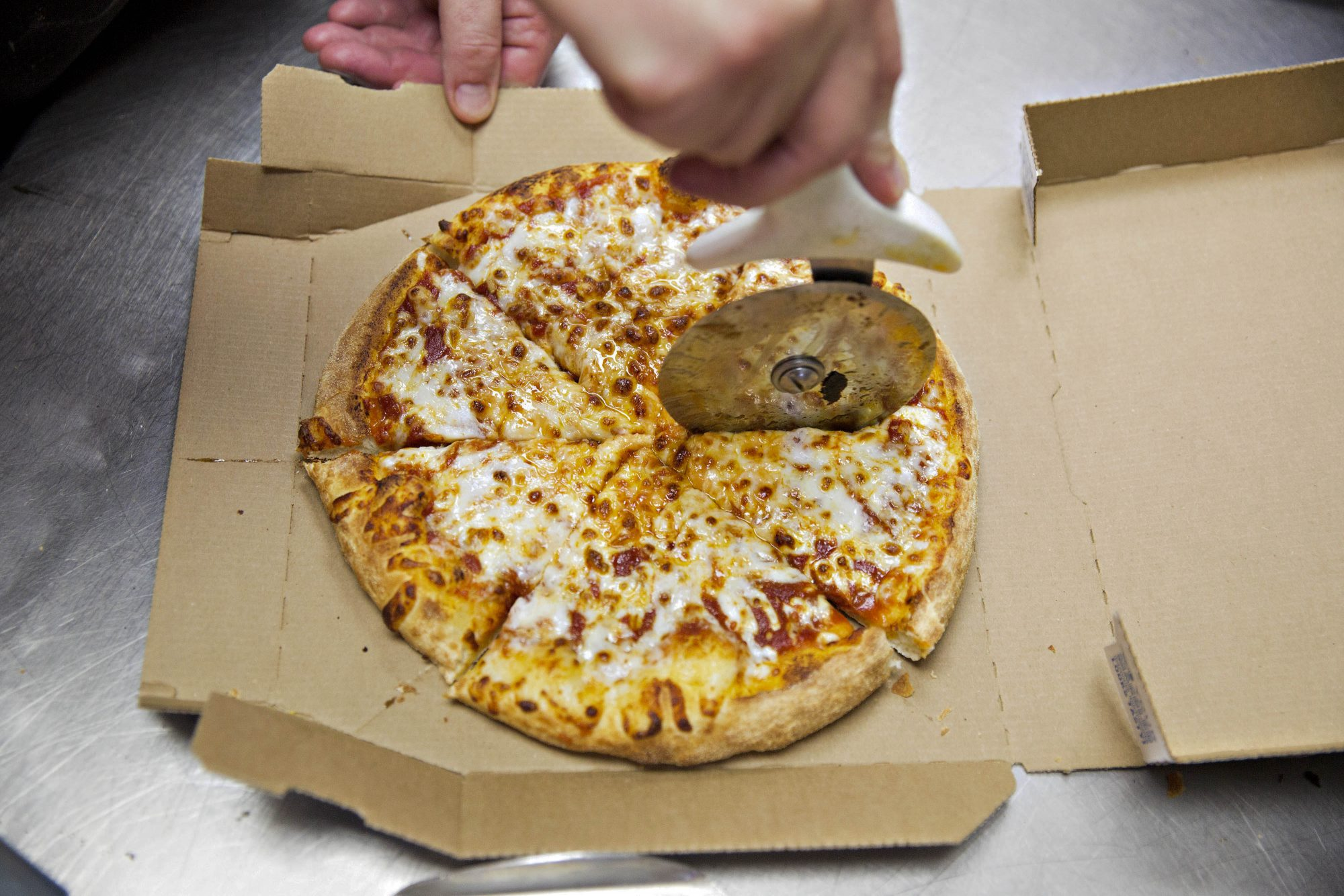 A pizza is sliced at a Domino's Pizza restaurant in Rantoul, Illinois, U.S., on Thursday, Oct. 8, 2015.