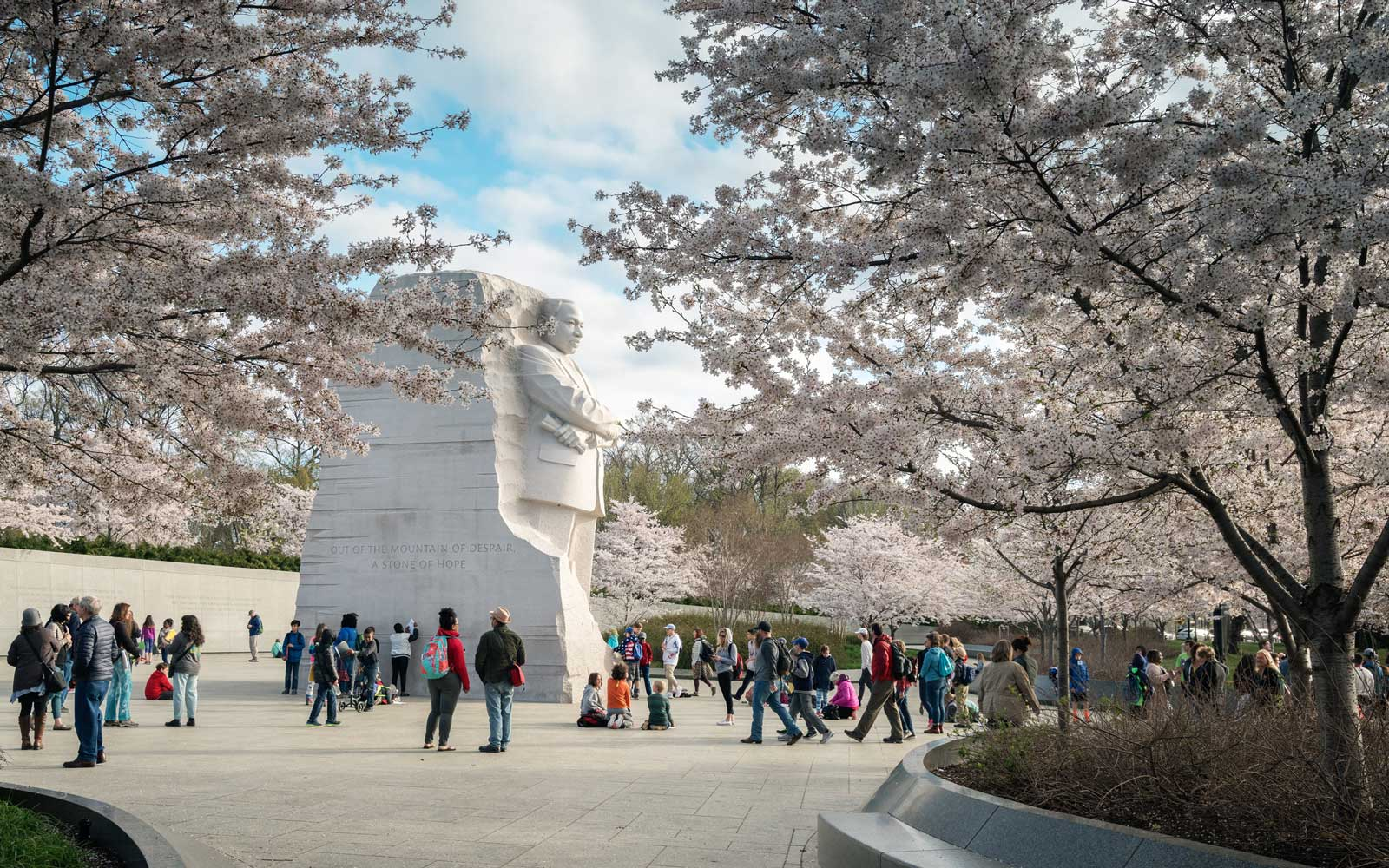 Blooming cherry trees and tourists surround the Martin Luther King, Jr. Monument at the Tidal Basin in Potomac Park.
