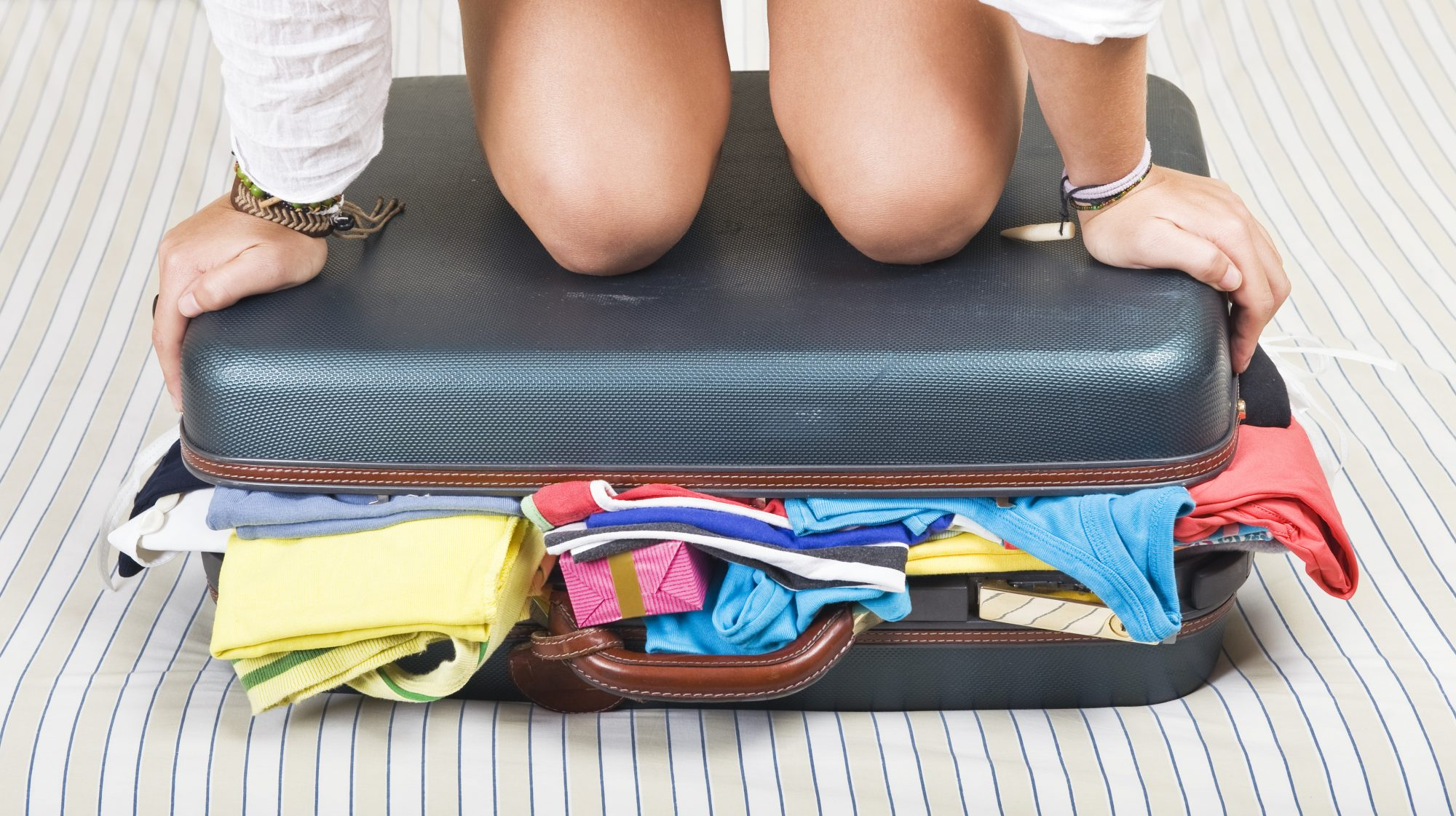 Woman Sitting on Suitcase to Close It