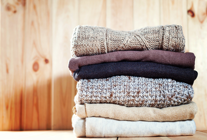 Knit cozy sweater folded in a pile on wooden background .Warm the concept