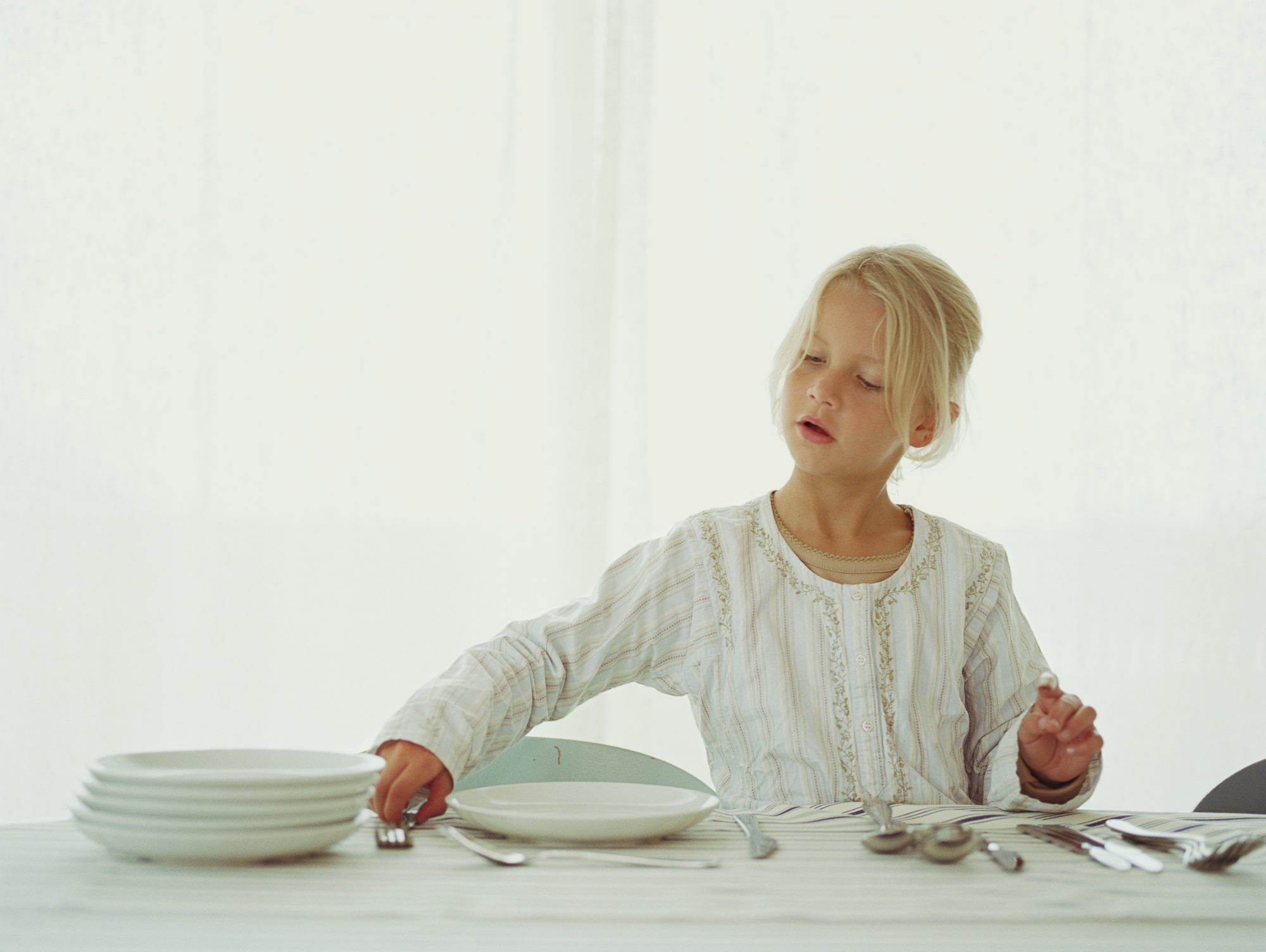 Young Girl Setting Table