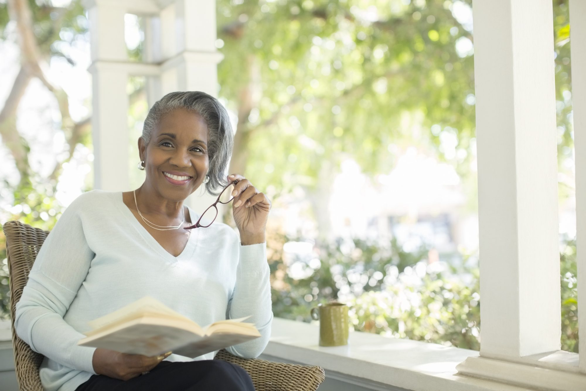 Woman Reading Book on Porch