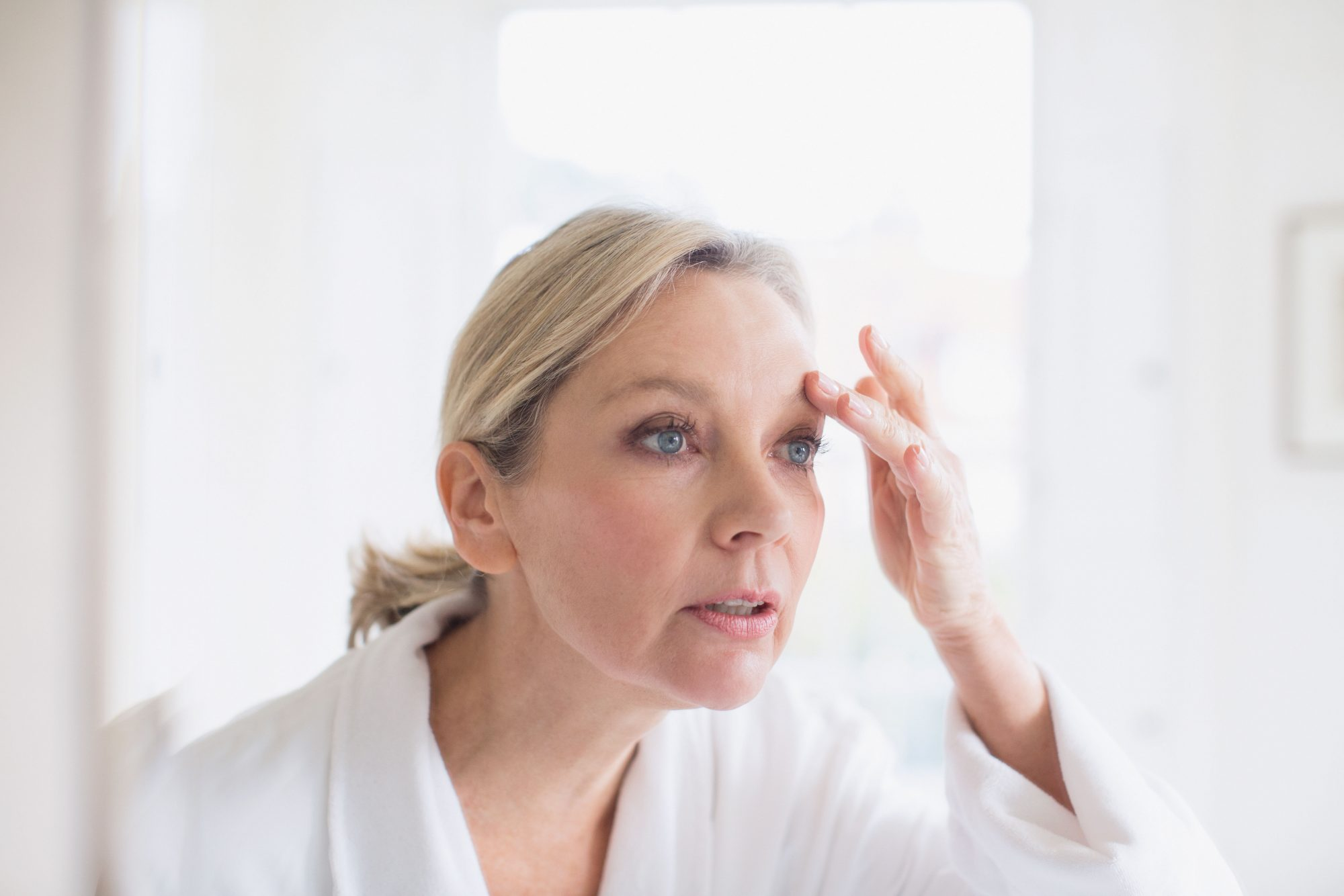 Woman Looking at Eyebrows in Mirror