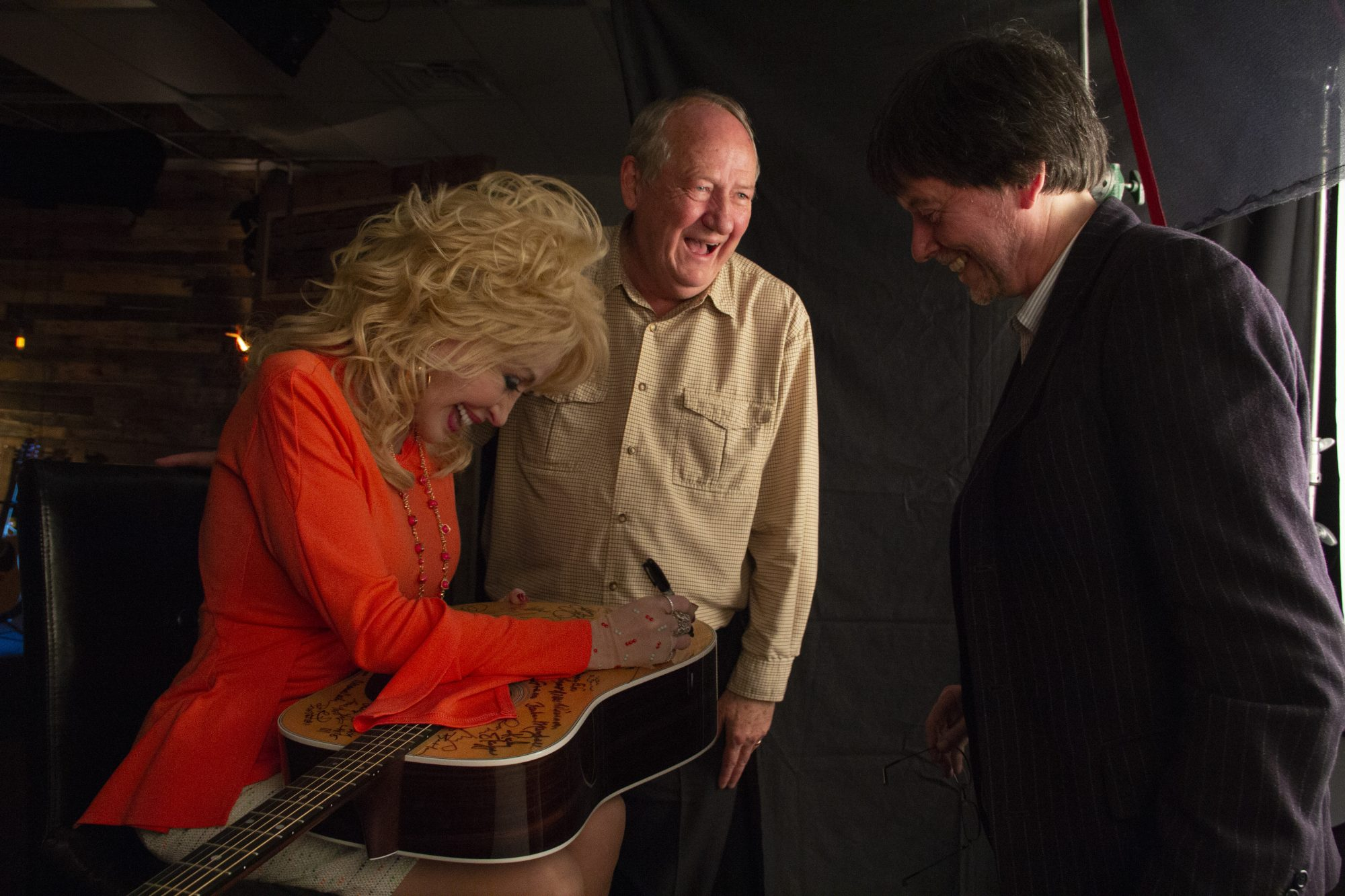 Dolly Parton Signs Guitar With Dayton Duncan and Ken Burns