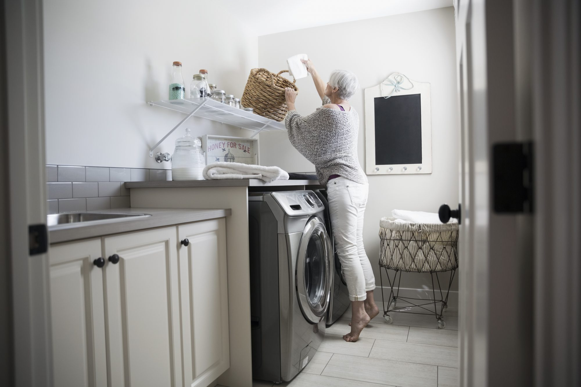 Older Woman Reaching in Basket Doing Laundry
