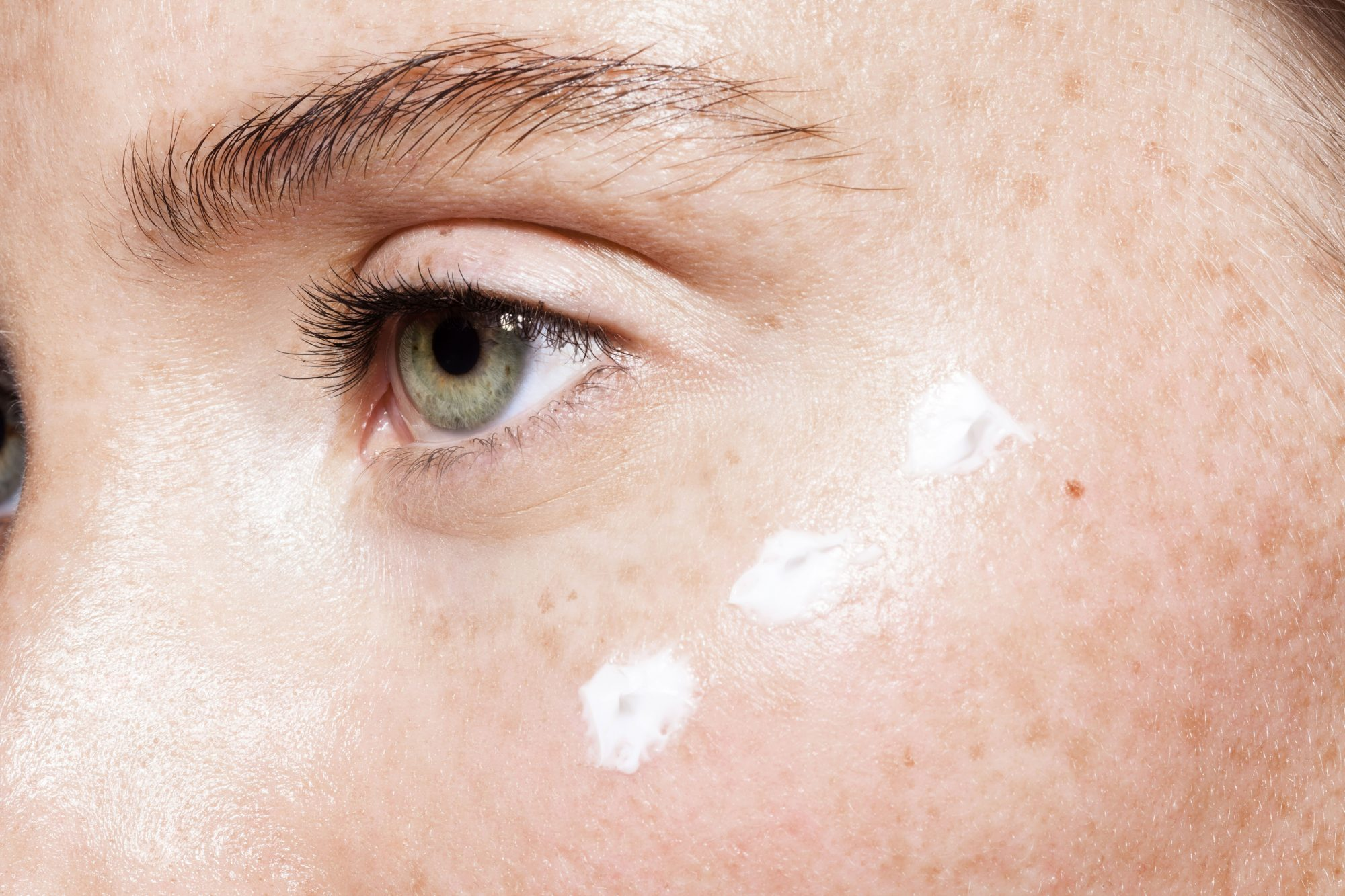 Woman Applying Face Cream Around Eyes