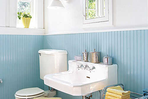 robin's egg blue beaded board lines the bottom half of the remodeled bathroom with white walls above as well as a new white sink, white medicine cabinet and a toilet to the left