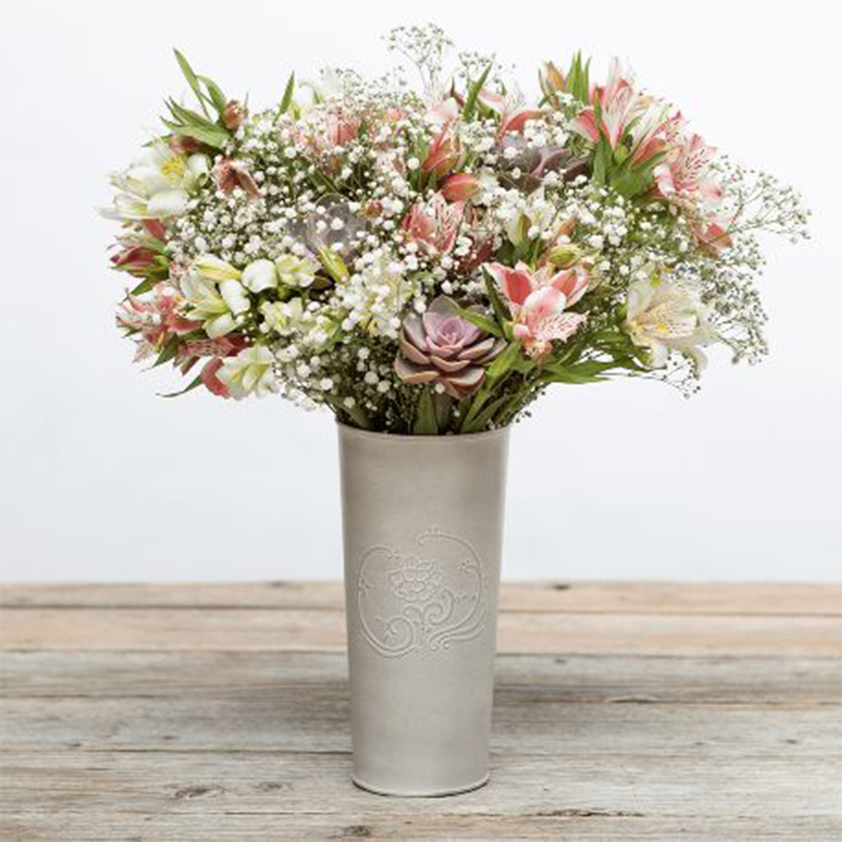 Tall vase filled with succulents, an alstroemeria, and other fresh flowers. photo