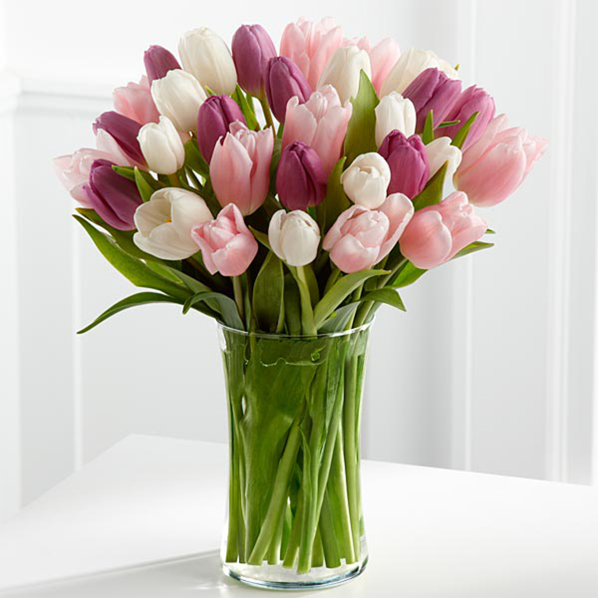 Clear glass vase holding pink, white, and purple tulips photo