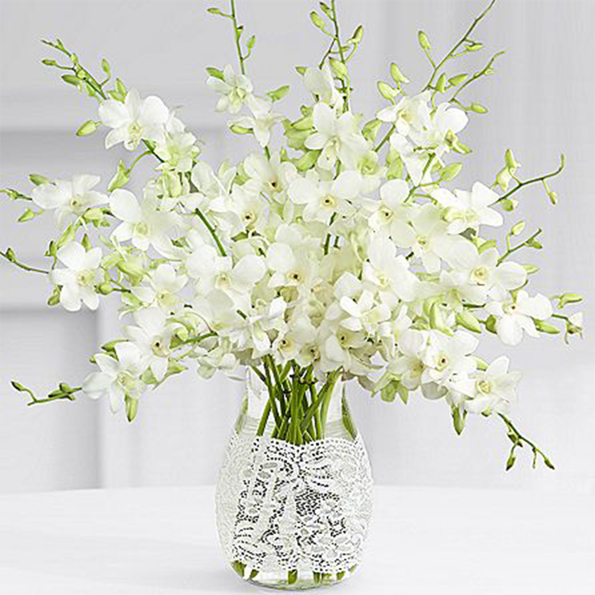 White vase with a lace design holding white flowers photo