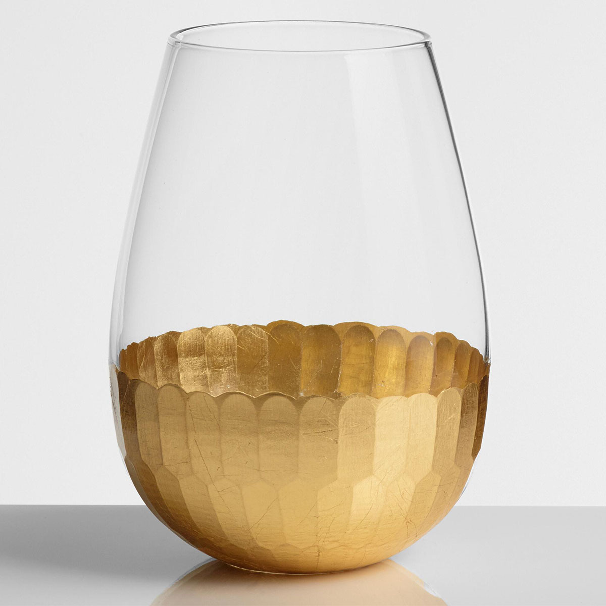 Clear wine glass with a dented gold bottom photo