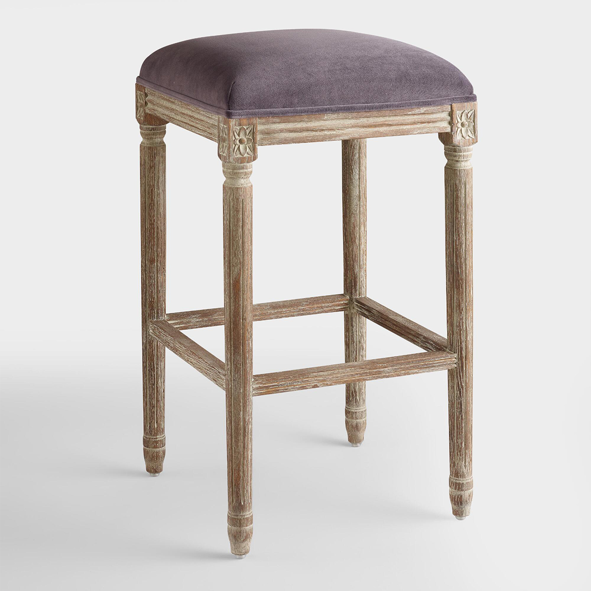 Tall barstool with a wooden frame a purple velvet fabric on top. photo