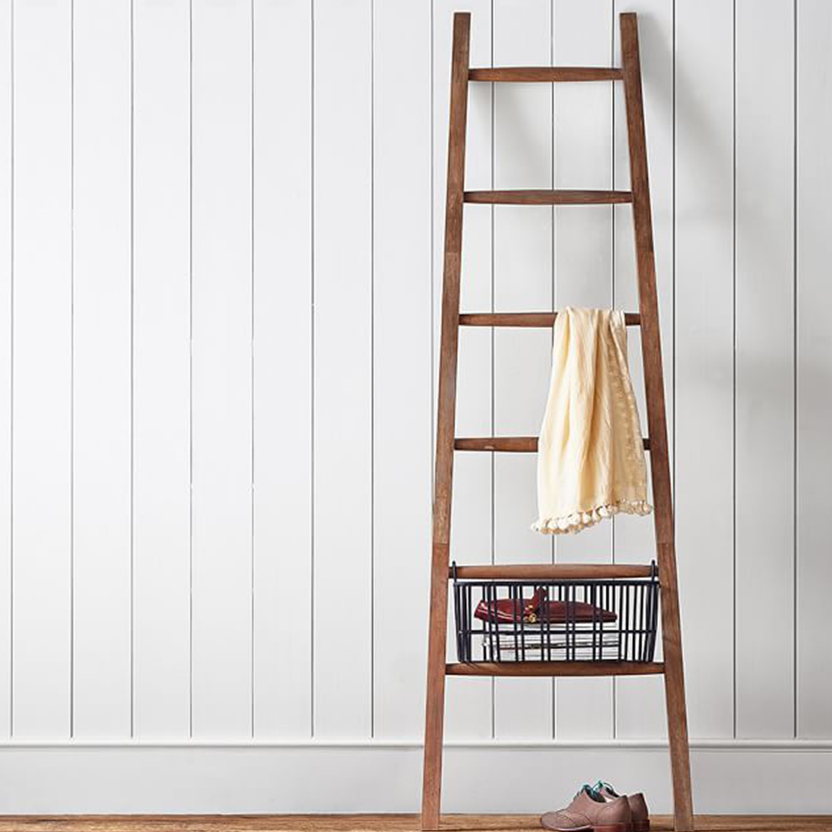 Wood ladder storing a small basket and throw blanket photo