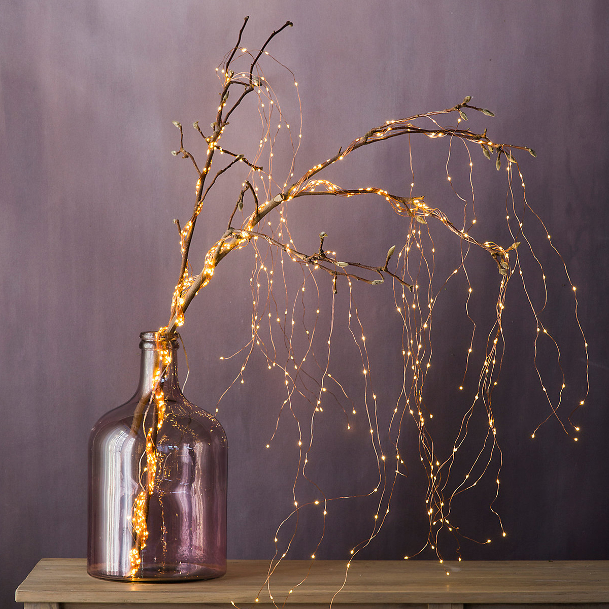 Terrain magnolia branches in a recycled glass vase with cascading lights photo