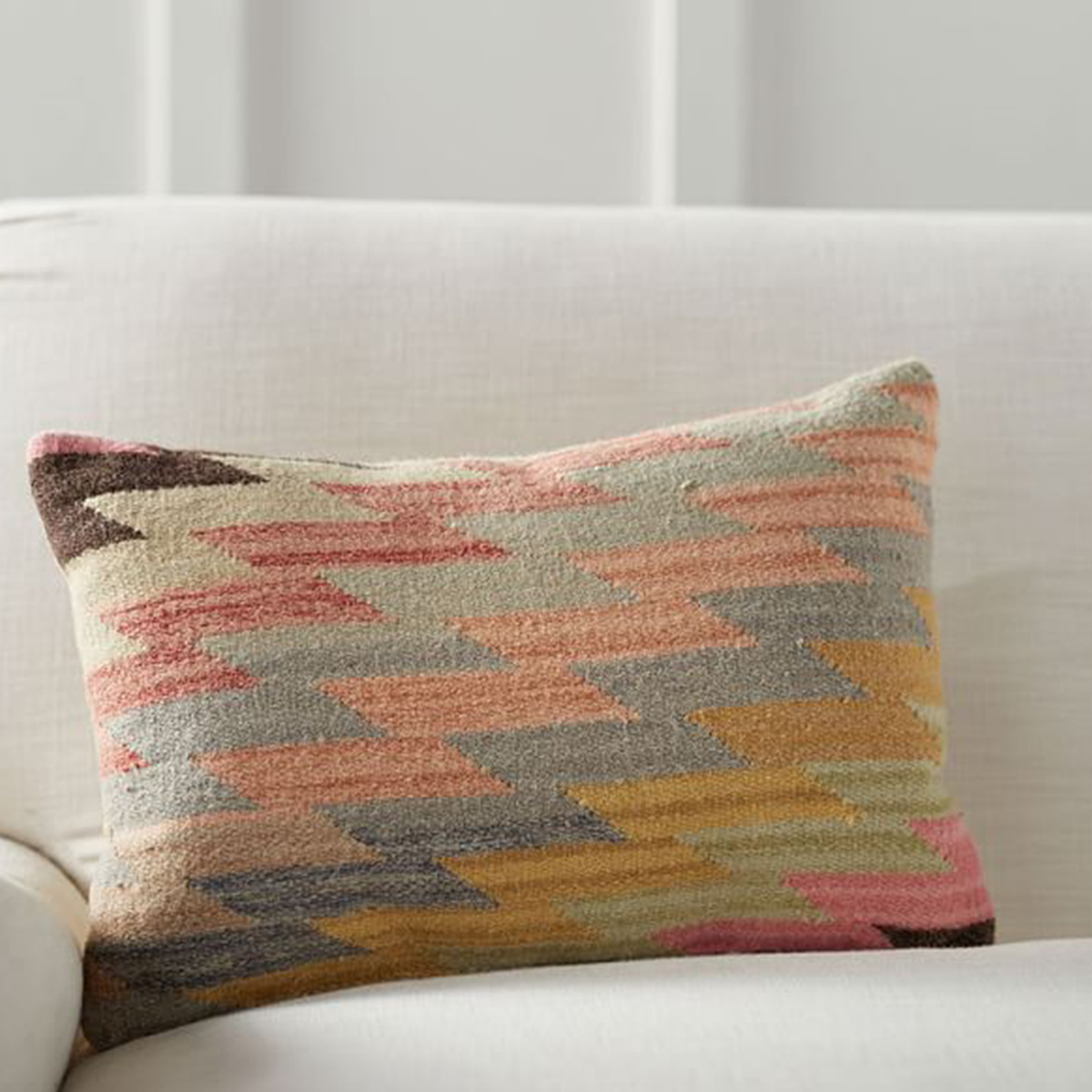 Southwest-inspired colorful handwoven pillow with a solid beige back. photo